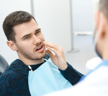 Young male patient holding his cheek in pain