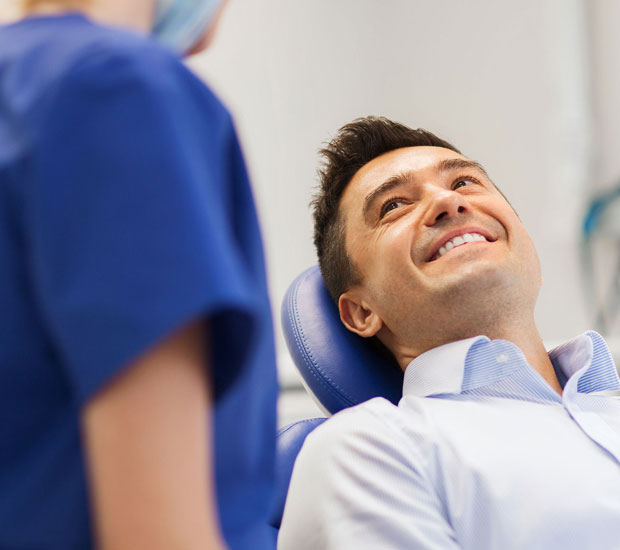 Middle-aged male patient smiling in the dental chair